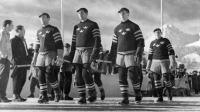 De svenska ishockeyspelarna tågar in på Isstadion i Sankt Moritz under öppningsceremonin vid de olympiska vinterspelen 1948 Foto: SVT